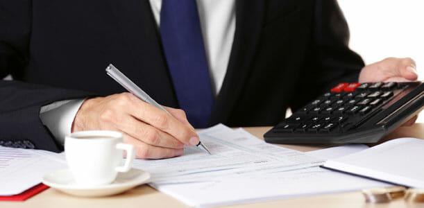 Man using a calculator to do taxes